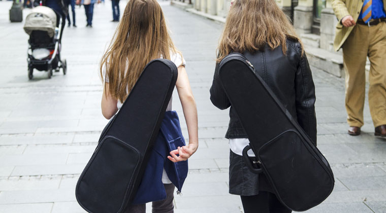 2 young girls walking down street with upgraded 21st century violin cases