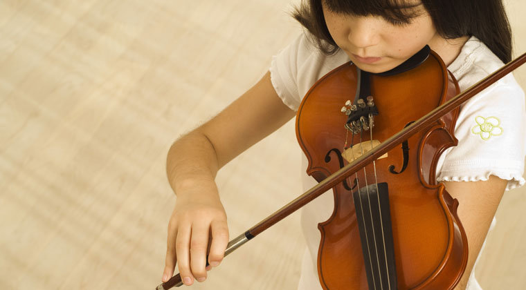 young girl practicing for better violin bowing