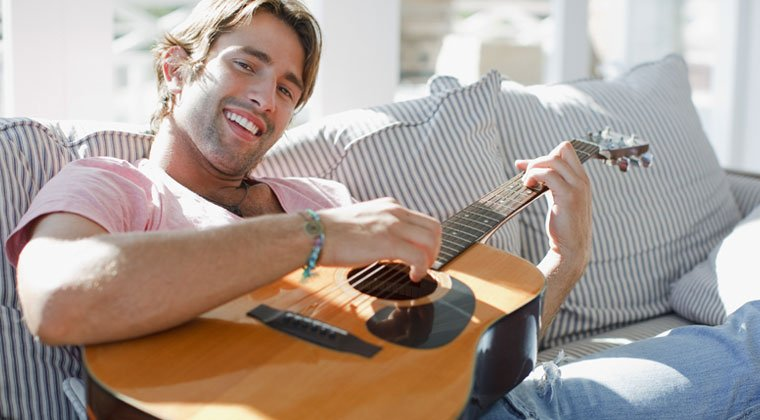 young man playing acoustic guitar smiling