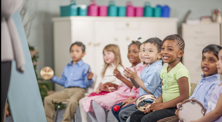 happy children in classroom playing musical instruments