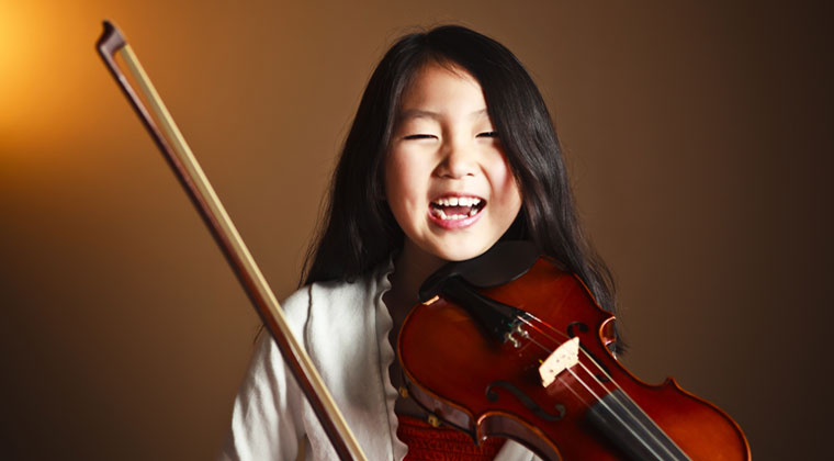 young girl laughing holding her first violin
