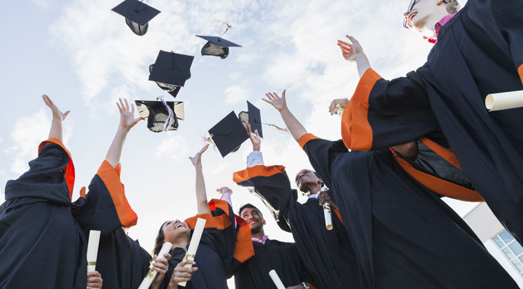 students graduating throwing there caps