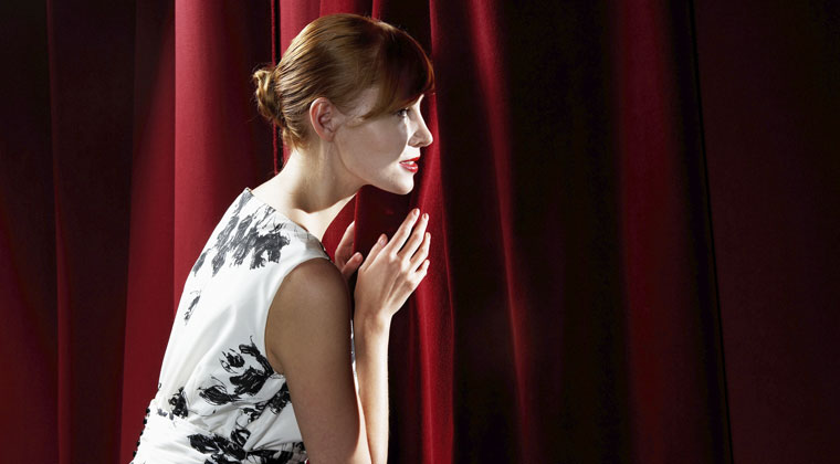 woman peeking out curtain on stage having stage fright