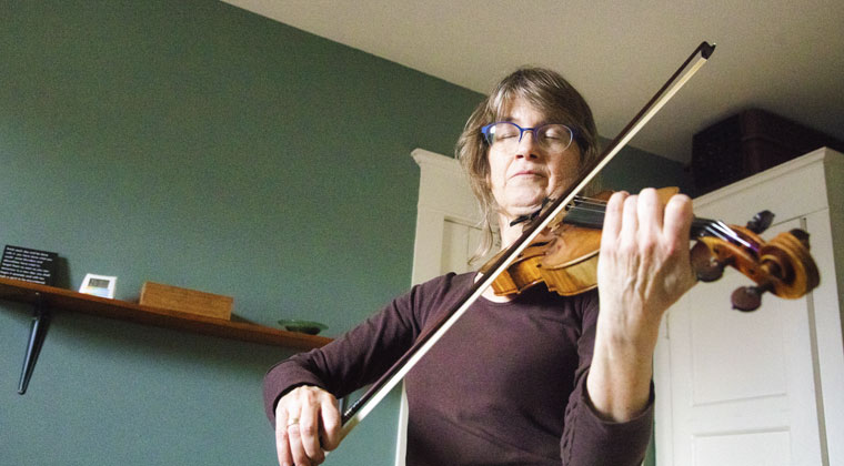 Adult violin learner practicing