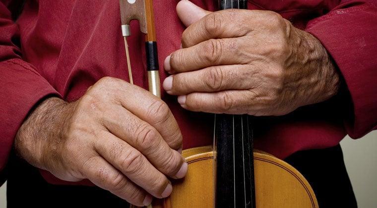 older mans hands holding violin
