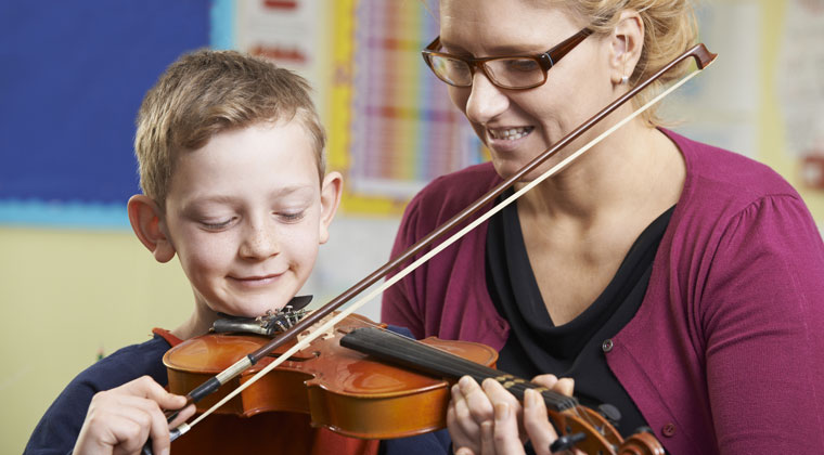 young boy being instructed by his violin teacher