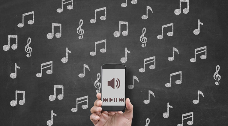 smart phone playing music composition against background of notes on a chalkboard