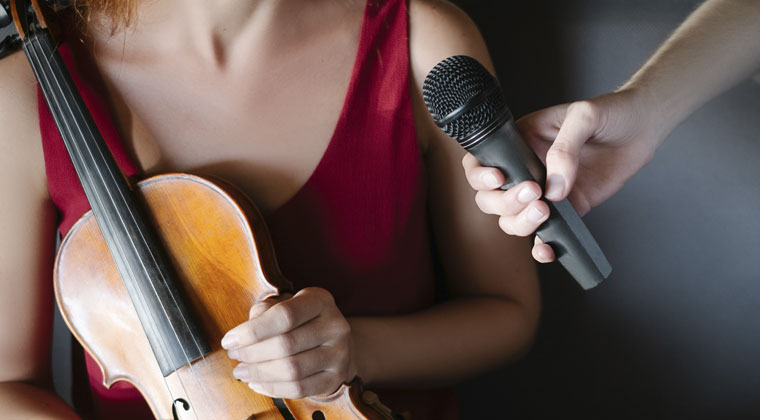 a violinist with a good public speaking voice talking on the microphone