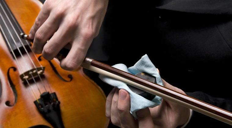 violinist using rosin on his instrument