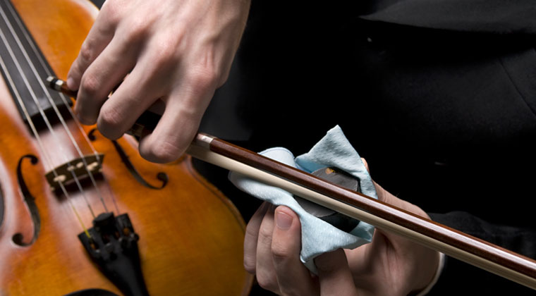 violinist using rosin on his instrument