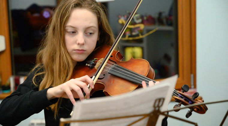 young girl practicing different bowing techniques on the violin