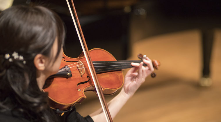 woman playing violin in fall music competition