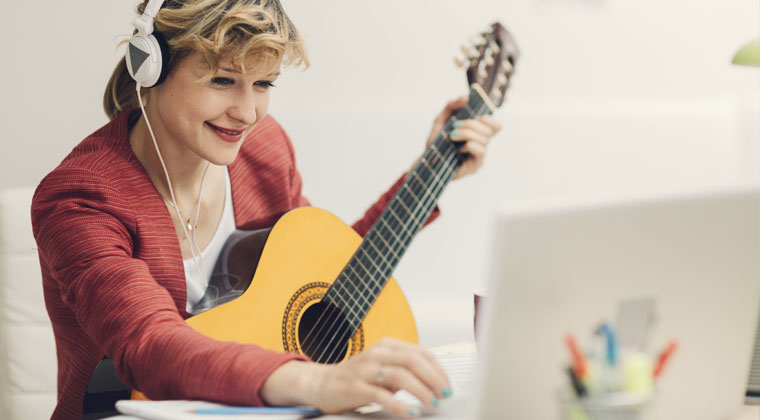 musician looking online for free music while playing guitar