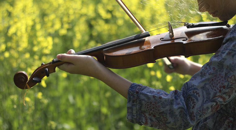 young girl playing violin outside getting inspired