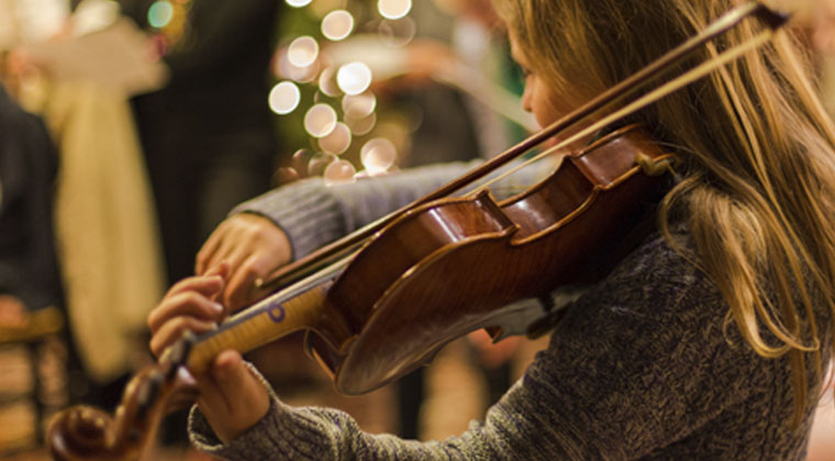 young girl performing violin during the holidays for a retirement home