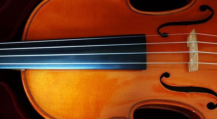 Close up of violin and how to care for its strings