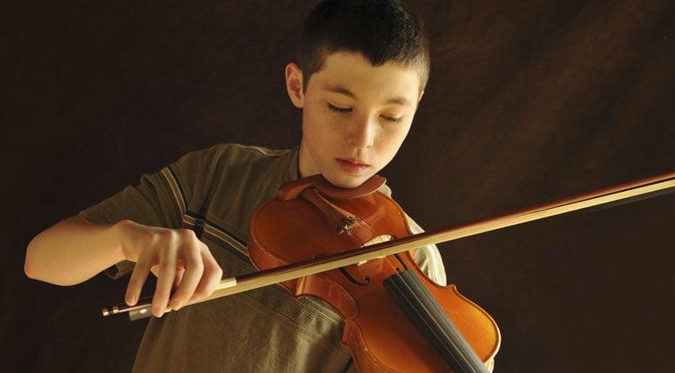 child practicing violin during his summer break