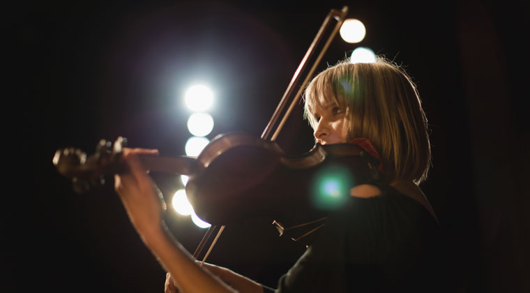 violinist performing solo program on stage