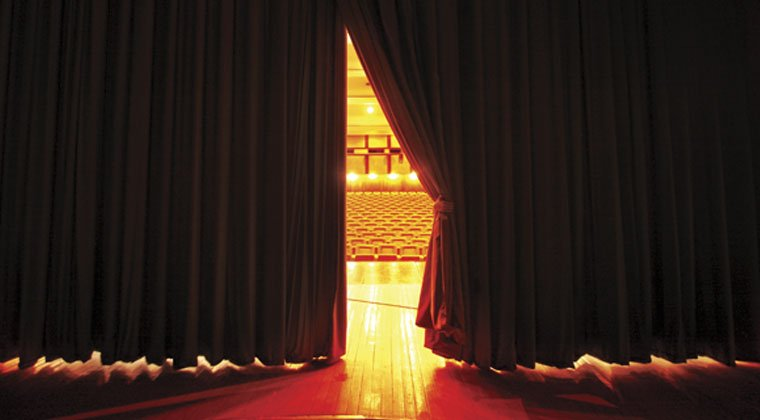 view of stage behind the curtain peaking out into the audience and thinking how to develop stage presence