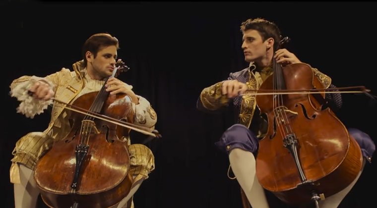 2CELLOS Luka Sulic and Stjepan Hauser playing Thunderstruck onstage wearing clothes from the 17th century Europe fashion