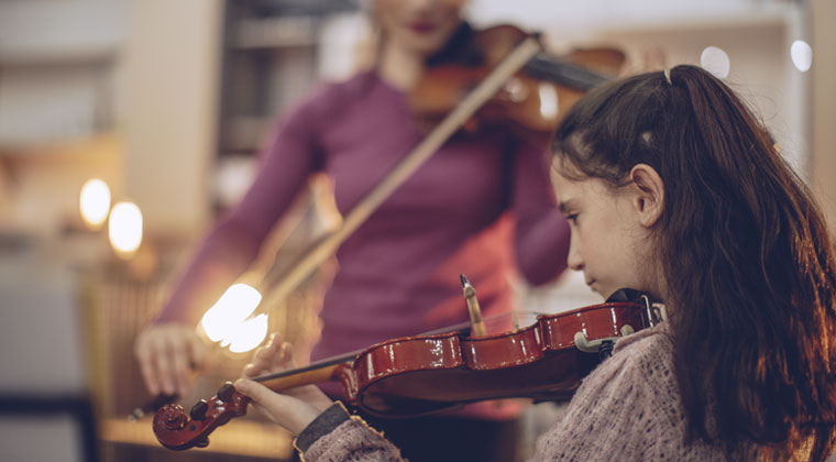 A student being taught to play the violin by her music teacher.