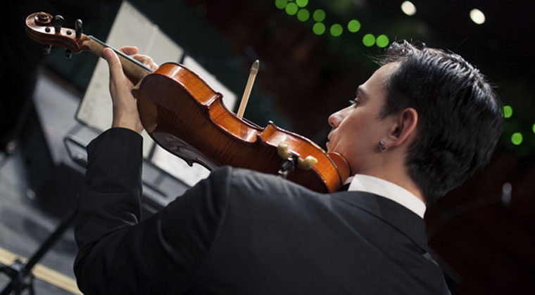 young man in a suit having a memorable violin audition