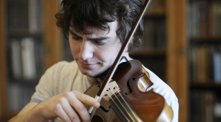 violinist listening to himself play trying to improve his tone