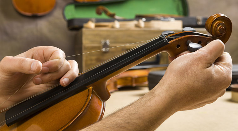 man replacing violin string