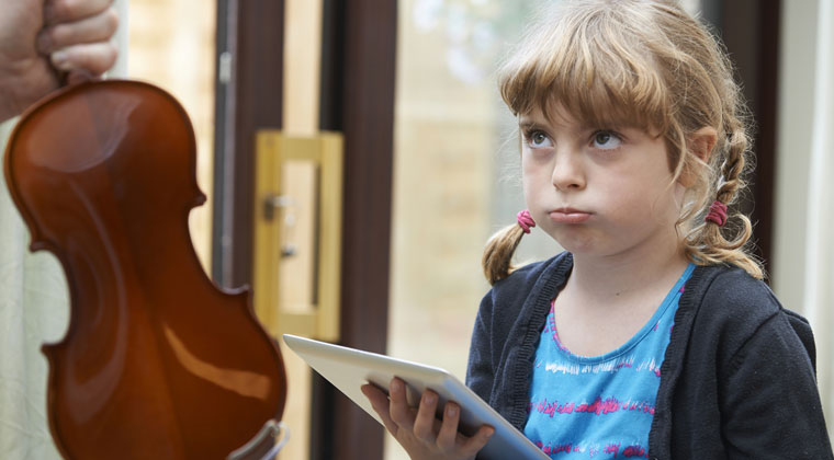 young violinist looking bored with learning the violin