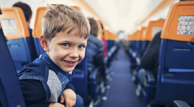 young child traveling on the plane with his string instrument