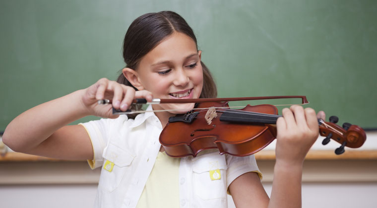 young girl using music improvisation with violin in classroom