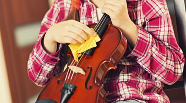 young violinist polishing her instrument