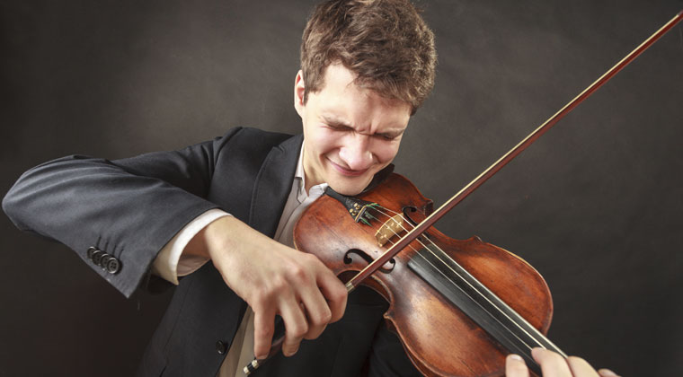 young man playing violin with intense facial expression