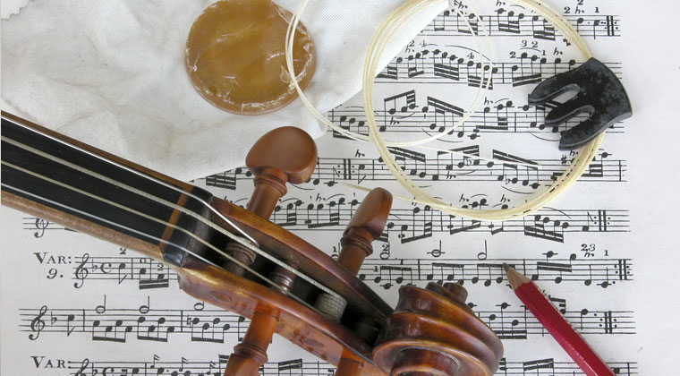 multiple violin accessories laying on sheet music