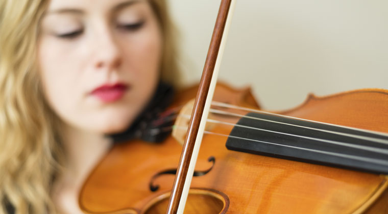 woman playing violin learning from new app