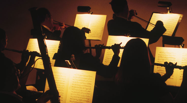 dark silhouettes and lit up sheet music of musical theatre pit orchestra