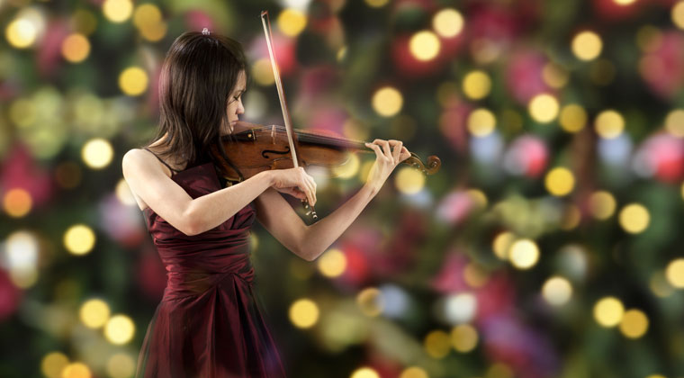 young woman playing the violin in front of holiday decor and paying it forward during the holidays