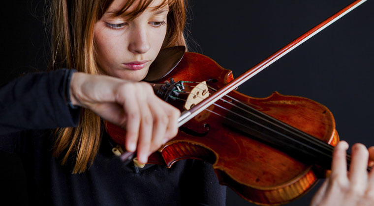 young girl playing violin and trying to learn how to incorporate dance and movement into her performace