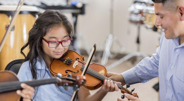 great violin teacher teaching young child
