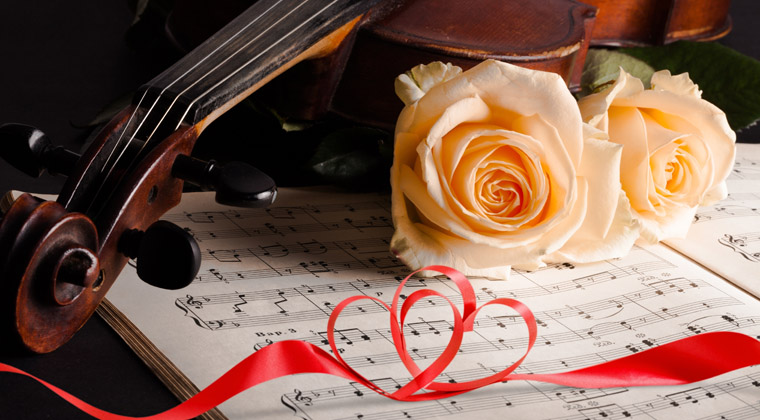 closeup of violin , sheetmusic, peached-colored roses and red ribbon shaped like hearts