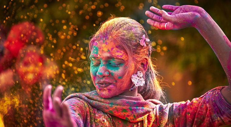 young woman dancing to sacred music at holi hindu spring holiday