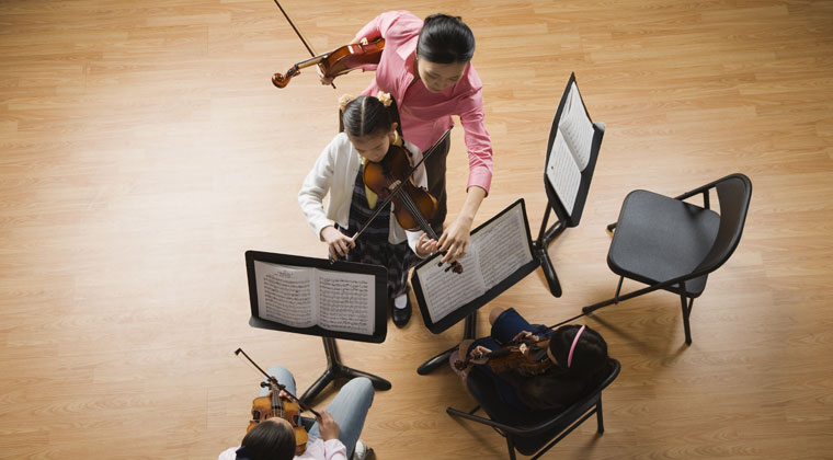 music teacher working with studetns to bring out the best in them