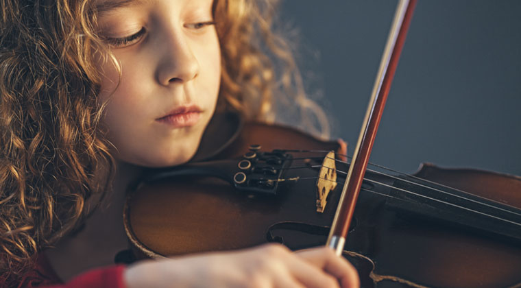 young girl practicing violin at home