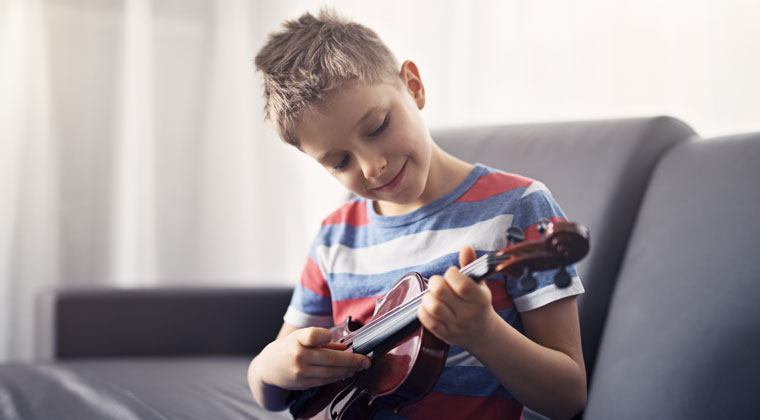 young boy playing string instrument and listening to harmonics