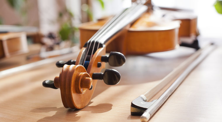 Close up of violin and bow on table, focusing on its strings