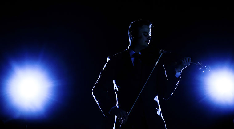 male violinist performing onstage persona brand with blue lights