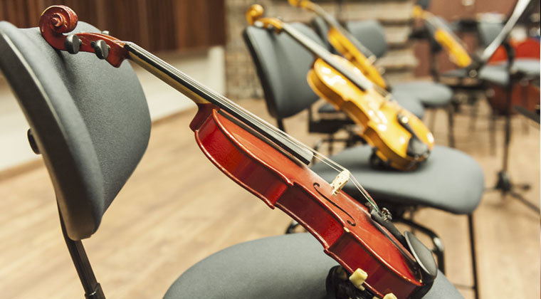 violins sitting on chairs in a concert hall ready for rehearsal for students to have fun rehearsing