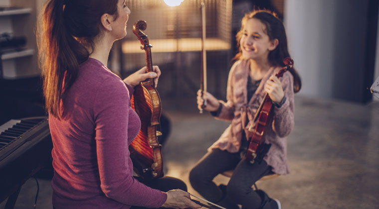 violin teacher having an fun and effective individual music lesson with a young student