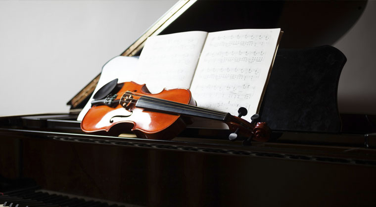 violin placed on top of grand piano in a four year music school