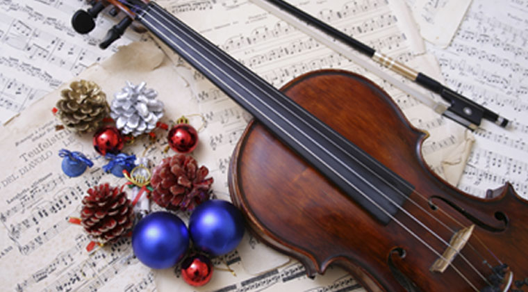 violin laying on holidat sheet music with holiday ornaments